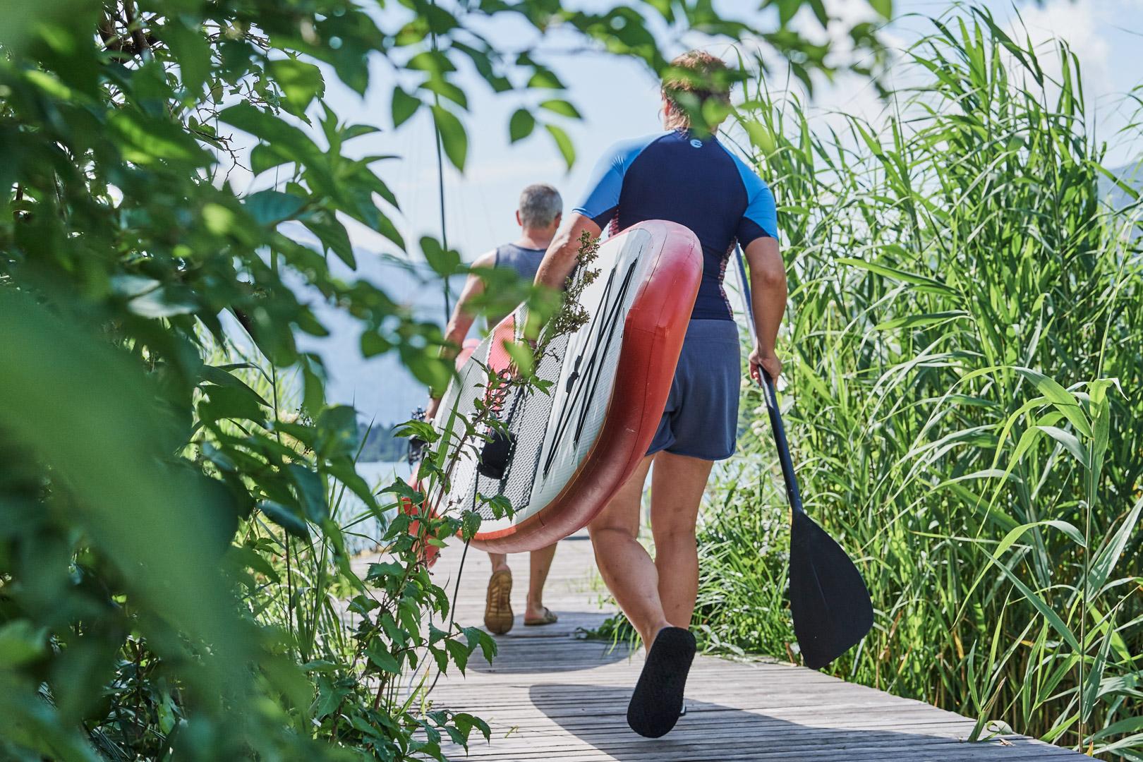 Männer tragen SUP auf einem Steg Richtung See