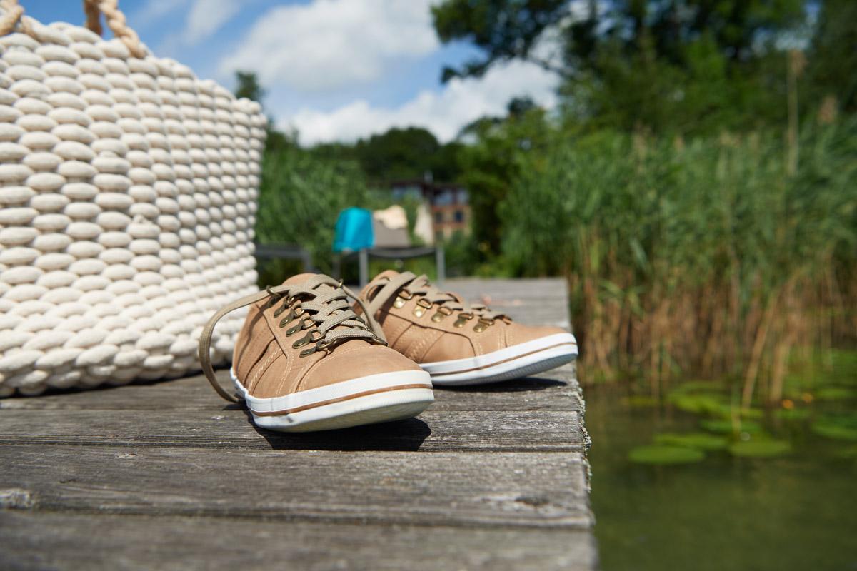 Schuhe auf einem Steg am See im Detail